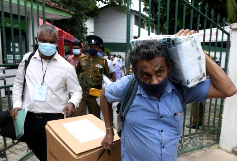 Officials collect ballot papers and boxes from a distribution centre in Colombo