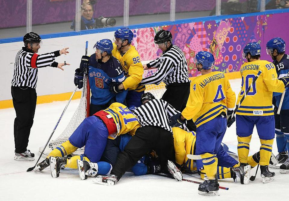 SOCHI, RUSSIA – FEBRUARY 21: Referees break the start of a fight during the Men's Ice Hockey Semifinal Playoff between Sweden and Finland on Day 14 of the 2014 Sochi Winter Olympics at Bolshoy Ice Dome on February 21, 2014 in Sochi, Russia. (Photo by John Berry/Getty Images)