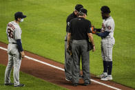 Houston Astros assistant pitching coach Bill Murphy, left, looks on as relief pitcher Cristian Javier has his gear inspected by first base umpire Ted Barrett, back left, and home plate umpire Angel Hernandez during the sixth inning of a baseball game, Monday, June 21, 2021, in Baltimore. (AP Photo/Julio Cortez)