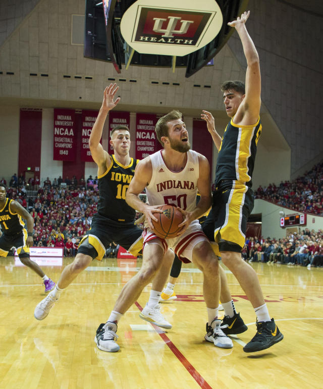 Indiana forward Joey Brunk (50) is stopped by the defense of Iowa guard Joe Wieskamp (10), left, and center Luka Garza (55) during the first half of an NCAA college basketball game, Thursday, Feb. 13, 2020, in Bloomington, Ind. (AP Photo/Doug McSchooler)