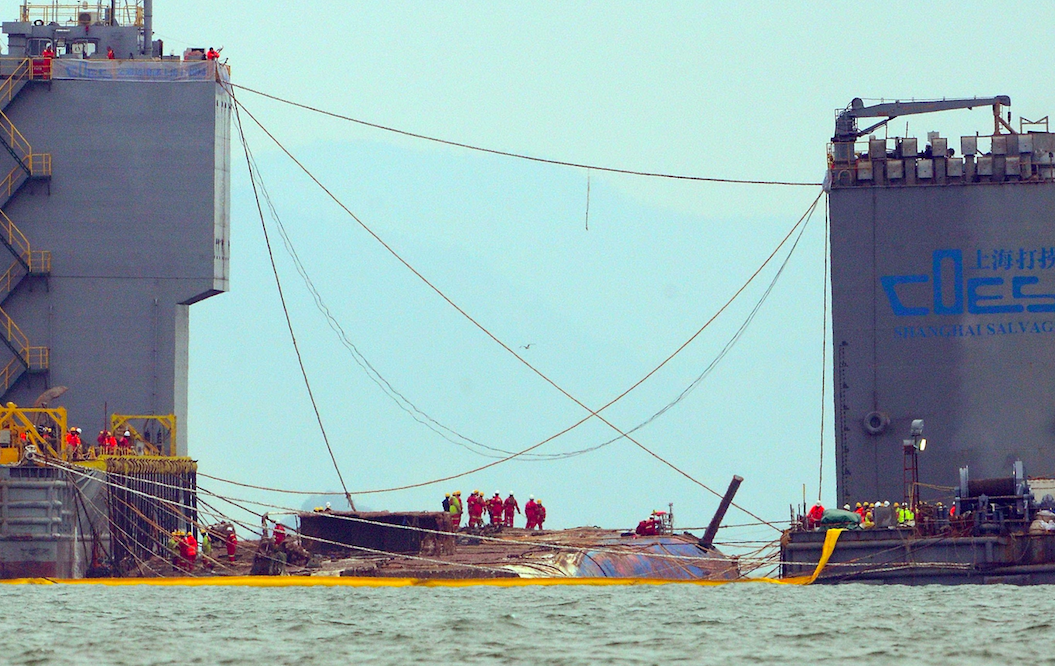 <p>Teams of salvage workers raise the Sewol ferry from the sea. (Picture: Rex) </p>