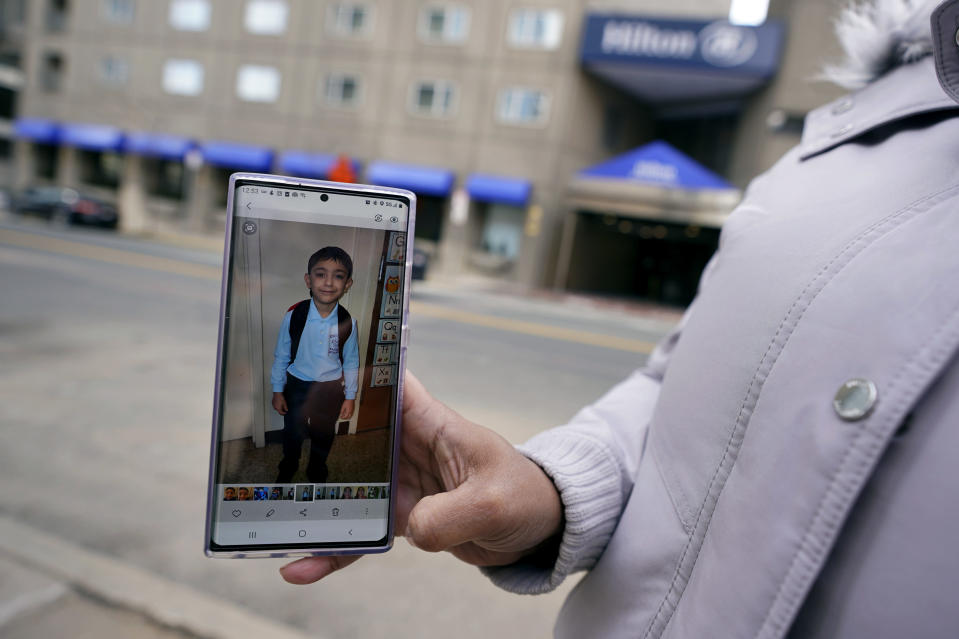 Hotel housekeeper Esther Montanez holds up a photograph of her five-year-old son Richard outside the Hilton Back Bay, Friday, March 5, 2021, in Boston. Montanez refuses to give up hope of returning to her cleaning job at the hotel, which she held for six years until being furloughed since March 2020 due to the COVID-19 virus outbreak. The single mother cannot bear the idea of searching for work that will almost certainly mean earning near the minimum wage. She earned about $23 a an hour at her job, plus tips, enough to provide a stable life for her son. (AP Photo/Charles Krupa)