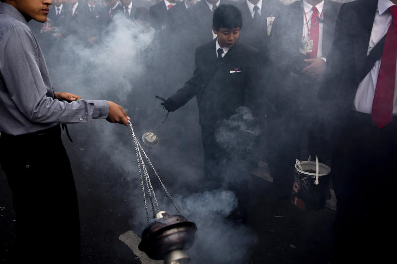 "In this April 16, 2019 photo, boys swing burners with incense purifying the path of the Holy Tuesday procession known as ""La Reseña,"" in downtown Guatemala City. The Holy Week procession, dating back centuries, parades the La Merced church statues of Jesus of Nazareth and Our Lady of Sorrows as worshippers throw bouquets of flowers onto the platforms. (AP Photo/Moises Castillo)"