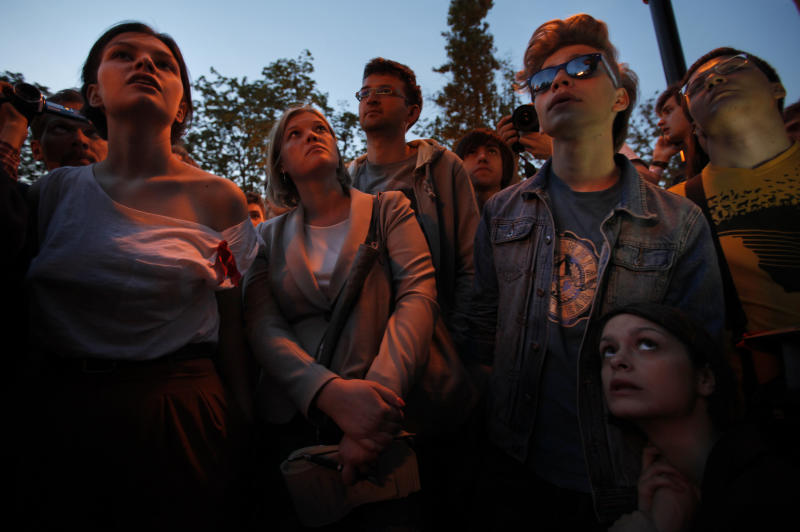Russian youth opposition followers, evicted by police from a protest camp at Chistiye Prudy, listen to an orator at a new site chosen for their camp next to Barrikadnaya (Barricade's) subway station in downtown Moscow, Russia, Thursday, May 17, 2012, with one of seven sky-scrapers built by Soviet dictator Josef Stalin is at the background.A prominent Russian opposition leader was sentenced Thursday to 10 days in jail, a day after being arrested at a rally as activists try to keep up the pressure on President Vladimir Putin and his government. On Thursday, Dmitry Medvedev, Putin's predecessor in the Kremlin and now prime minister, warned that authorities must become more flexible about protests.(AP Photo/Alexander Zemlianichenko)