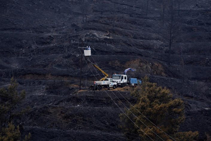 """Electricity power engineers at work, in the burned Larnaca mountain region near Ora village, Cyprus, Sunday, July 4, 2021. Cyprus' interior minister says four people have died in what he called the """"most destructive"""" fire in the island nation's history. (AP Photo/Petros Karadjias)"""