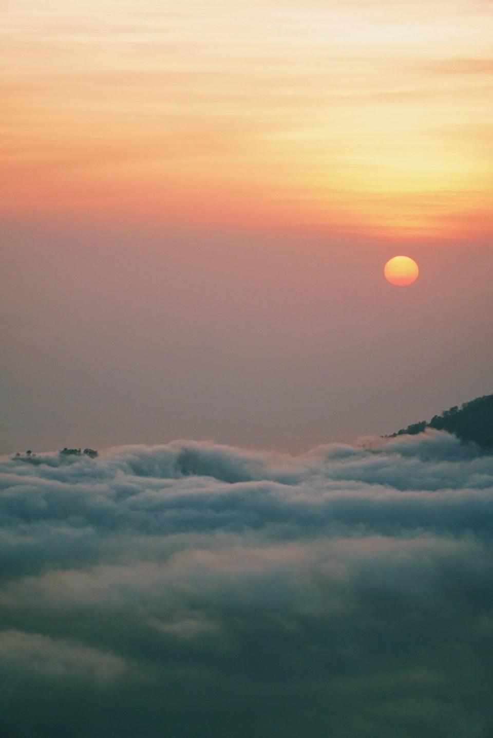 The sun rising over Mount Batur and the clouds.