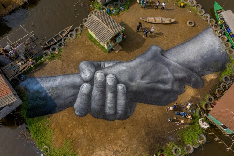 Guillaume Legros, also known as Sype, painted vast joined hands in Benin as part of a chain of similar works around the world
