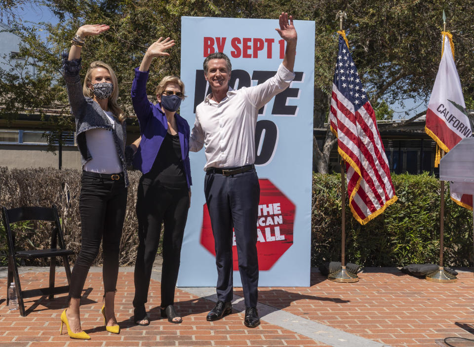 California first lady Jennifer Siebel Newsom, left, and Sen. Elizabeth Warren, D-Mass., middle, join California Gov. Gavin Newsom at a campaign event against the gubernatorial recall election at the Culver City High School in Culver City, Calif., Saturday, Sept. 4, 2021. (AP Photo/Damian Dovarganes)