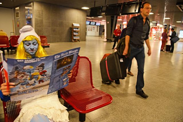 BRUSSELS, BELGIUM - JUNE 22: A Smurf Ambassador reads a special edition of a fake newspaper, designed for the Global Smurfs Day event, in the waiting lounge as Smurf Ambassadors prepare to board a branded high speed train from Brussels to Paris as part of Global Smurfs Day celebrations on June 22, 2013 at Brussels railway station, Belgium. (Photo by Pascal Le Segretain/Getty Images for Sony Pictures Entertainment)