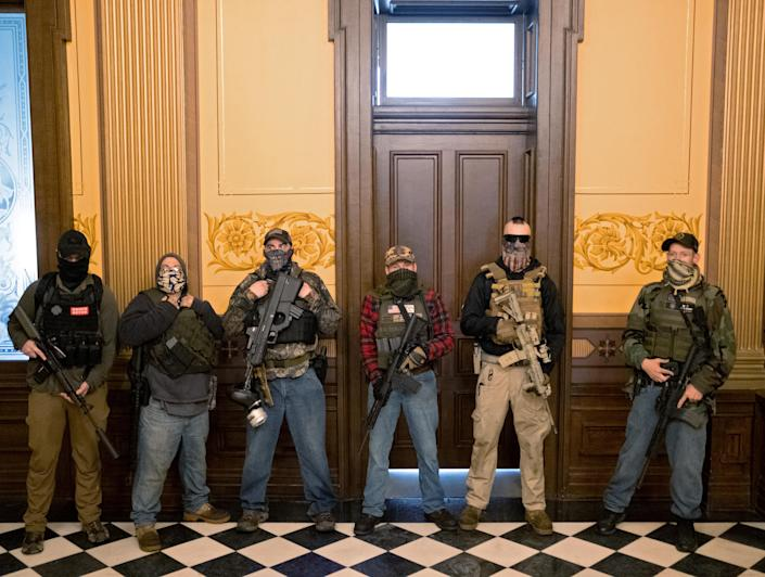 A militia group with no political affiliation from Michigan stands in front of the governor's office on April 30 after protesters occupied the state Capitol during a vote to approve the extension of Gov. Gretchen Whitmer's stay-at-home order due to the coronavirus outbreak. (Seth Herald/Reuters)