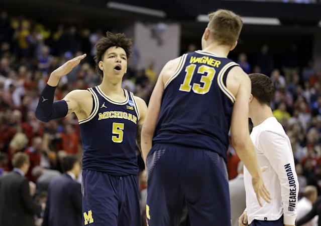 Michigan forward Moritz Wagner (13) and forward D.J. Wilson (5) celebrates a 73-69 win over Louisville in a second-round game in the men's NCAA college basketball tournament in Indianapolis, Sunday, March 19, 2017. (AP Photo/Michael Conroy)