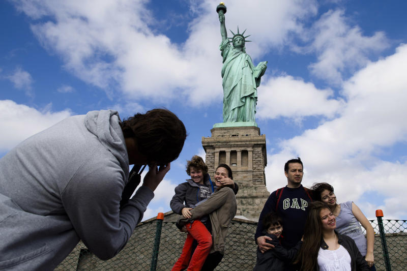 Tourists pose for photographs in front of the Statue of Liberty in New York Harbor, Sunday, Oct. 13, 2013, in New York. The Statue of Liberty reopened to the public after the state of New York agreed to shoulder the costs of running the site during the partial federal government shutdown. (AP Photo/John Minchillo)