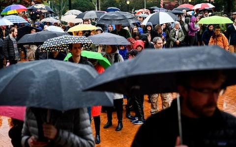 People carried umbrellas and a message of unity - Credit: Brendan Smialowski/AFP