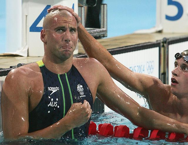 ATHENS - AUGUST 21: Grant Hackett (L) of Australia cries after winning the gold medal as bronze medalist David Davies of Great Britain congratulates him after swimming in the men's swimming 1500 metre freestyle final on August 21, 2004 during the Athens 2004 Summer Olympic Games at the Main Pool of the Olympic Sports Complex Aquatic Centre in Athens, Greece. (Photo by Stuart Hannagan/Getty Images)