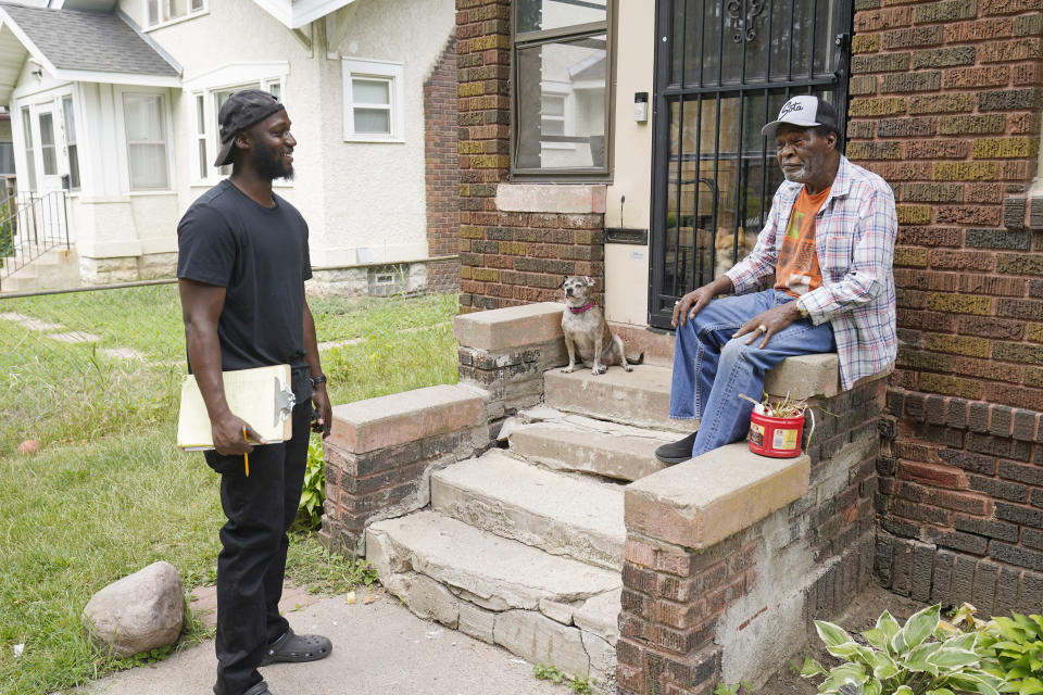 FILE - In this July 22, 2021, file photo, organizer Latrell Snider, left, talks with Minneapolis resident Steven Black ahead of the November election, as small armies of door-knockers are hitting the Minneapolis streets seeking to build support for a ballot question that would eliminate the city's police department and replace it with something new. Three Minneapolis residents are suing the city over a ballot question on how to change policing in the wake of George Floyd's death at the hands of police. They argue the ballot language city officials approved in August is misleading and fails to inform voters about key aspects of the proposal. (AP Photo/Jim Mone, File)