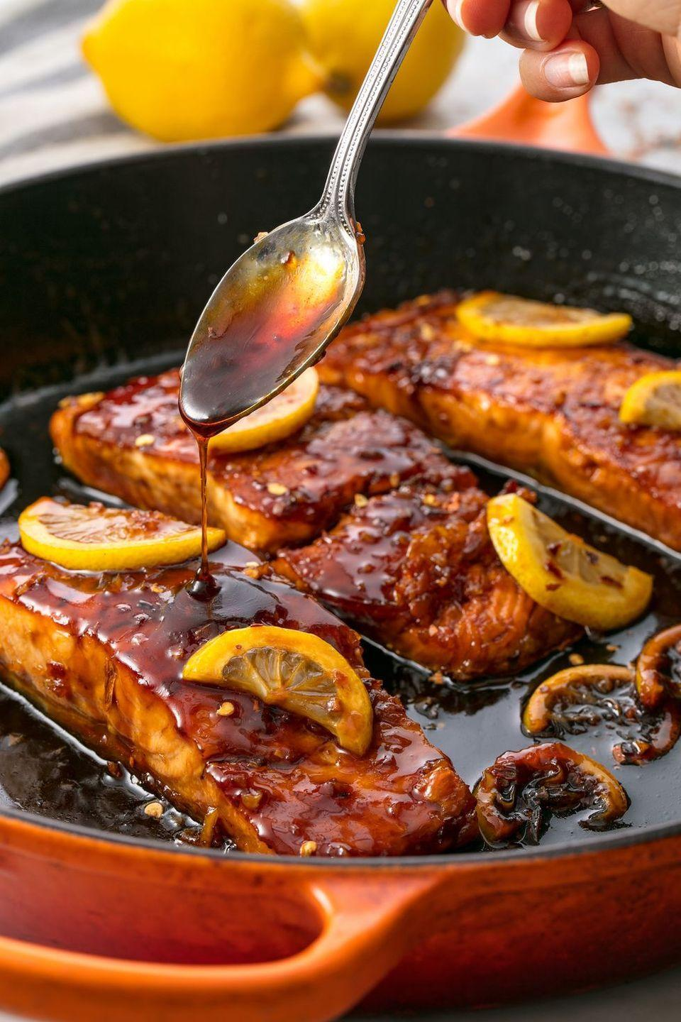 """<p>Searing fish might seem intimidating, but once you get the hang of it, it'll be second nature! It's important that you get your pan hot and the bottom of your pan thoroughly coated in oil.</p><p>Get the <a href=""""https://www.delish.com/uk/cooking/recipes/a28886105/honey-garlic-glazed-salmon-recipe/"""" rel=""""nofollow noopener"""" target=""""_blank"""" data-ylk=""""slk:Honey Garlic Glazed Salmon"""" class=""""link rapid-noclick-resp"""">Honey Garlic Glazed Salmon</a> recipe.</p>"""
