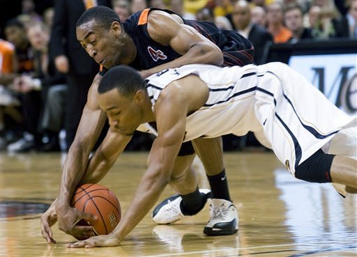 Oklahoma State's Markel Brown, top, and Matt Pressey, bottom, battle for a loose ball during the first half of an NCAA college basketball game Wednesday, Feb. 15, 2012, in Columbia, Mo. (AP Photo/L.G. Patterson)