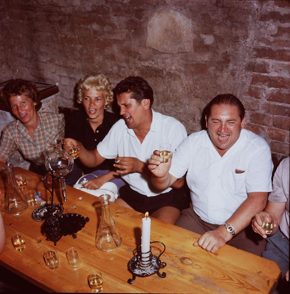<p>Bar patrons enjoy a carafe of wine in Hungary. Today, ruin bars are a popular cornerstone in Budapest. The trend took off in the early 2000s when formerly abandoned buildings were refurbished as watering holes.</p>