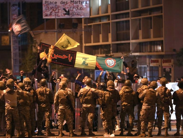Supporters of Lebanese Shiite groups Hezbollah and Amal wave flags and chant in front of army soldiers in the capital Beirut