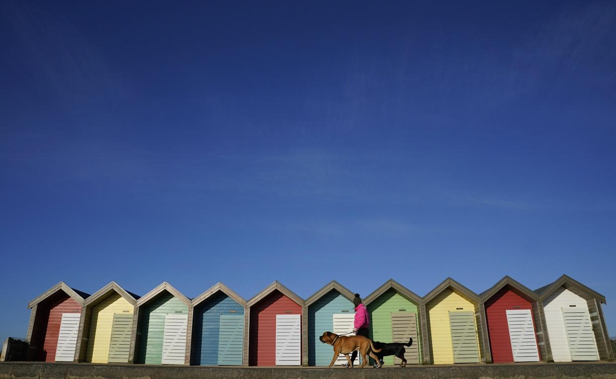 A woman walks her dog past beach huts at Blyth beach in Northumberland