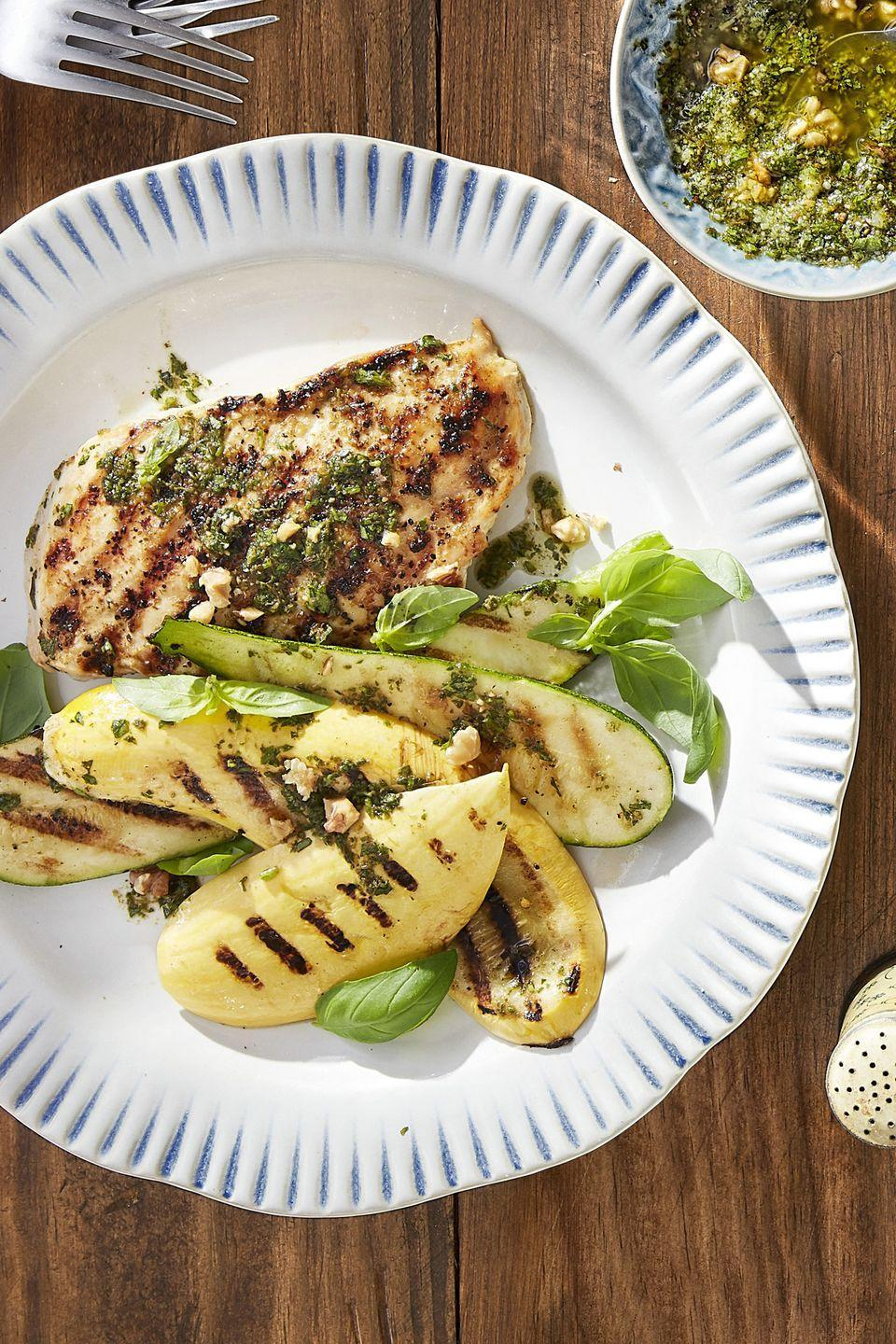 "<p>Let your grill do the work on the chicken and squash front while you prepare the pesto dressing.</p><p><a href=""https://www.countryliving.com/food-drinks/recipes/a44227/grilled-pesto-chicken-summer-squash-recipe/"" rel=""nofollow noopener"" target=""_blank"" data-ylk=""slk:Get the recipe."" class=""link rapid-noclick-resp""><strong>Get the recipe.</strong></a></p>"