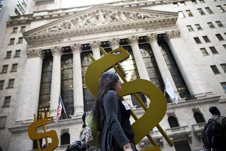 Occupy Wall Street demonstrators carry dollar signs past the New York Stock Exchange during a protest against the rising national student debt, in New York, April 25, 2012.