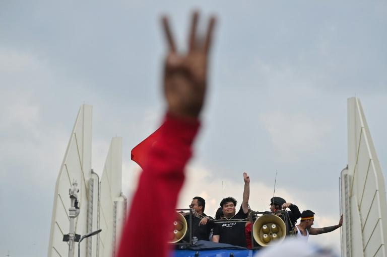 "Pro-democracy activist Parit ""Penguin"" Chiwarak gives the three-finger salute as they march towards Government House"