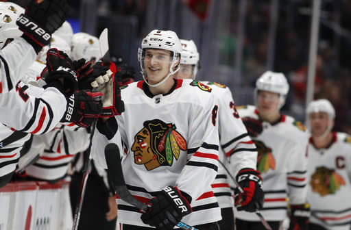 FILE - Chicago Blackhawks left wing Dominik Kubalik, center, smiles as he is congratulated while passing the team box after scoring the go-ahead goal against the Colorado Avalanche during the third period of an NHL hockey game in Denver, in this Saturday, Dec. 21, 2019, file photto. Chicago won 5-3. The Chicago Blackhawks are going to remain the Blackhawks and there is no sign of any change coming anytime soon. Speaking publicly for the first time Thursday, Dec. 17, 2020, since baseball's Cleveland Indians announced Monday they plan to change their name, Blackhawks CEO Danny Wirtz reiterated the same message the team shared this summer after lingering questions about Native American team names returned to the forefront.(AP Photo/David Zalubowski, File)