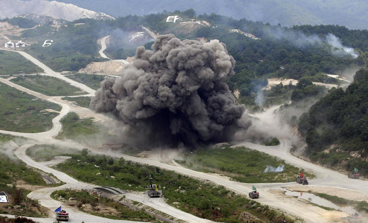 In this photo taken Tuesday, June 19, 2012, smokes are seen as heavy armored vehicles wait during a South Korea-U.S. joint military live-fire drills at Seungjin Fire Training Field in Pocheon, South Korea, near the border with North Korea. The drills were held in a show of combat readiness ahead of the 62nd anniversary of the start of the Korean War on June 25. (AP Photo/Lee Jin-man)