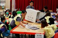 Polling officials open a ballot box to count the votes of the Hong Kong council elections, in a polling station in Hong Kong