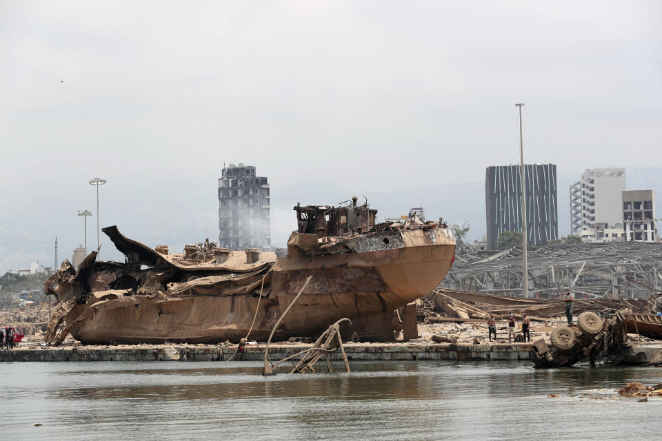 People stand by the wreckage of a ship at the devastated site of the explosion in the port of Beirut, Lebanon, Thursday Aug.6, 2020. French President Emmanuel Macron came in Beirut to offer French support to Lebanon after the deadly port blast.(AP Photo/Thibault Camus, Pool)