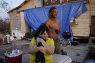 Yvonne Lacobon hugs a dog beside Tommy Williams at Williams' home damaged by Hurricane Ida, Saturday, Sept. 4, 2021, in Dulac, La. (AP Photo/John Locher)