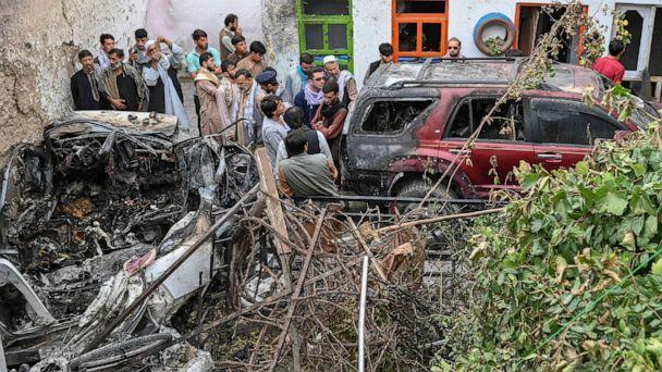 PHOTO: Afghan residents gather next to a damaged vehicle a day after a U.S. drone airstrike in Kabul on Aug. 30, 2021.  (Wakil Kohsar/AFP via Getty Images, FILE)