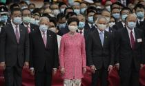 Hong Kong Chief Executive Carrie Lam, center, and former Chief Executives Tung Chee-hwa, fourth from right, and Leung Chun-ying, fifth from right, attend the flag raising ceremony at the Golden Bauhinia Square to mark the 71st anniversary of Chinese National Day in Hong Kong Thursday, Oct. 1, 2020. Others are, Chief Justice Geoffrey Ma, right, and Lam's husband Lam Siu-por. (AP Photo/Vincent Yu)
