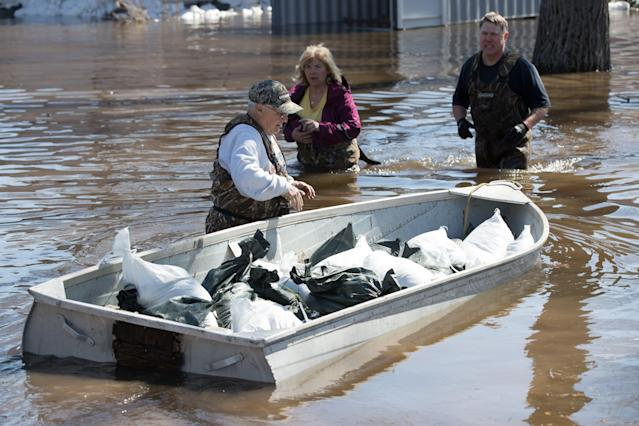 A man moves a boat full of sandbags to help with the flooding in Constance Bay, west of Ottawa, Ontario, on April 28, 2019. (Photo by Lars Hagberg / AFP)