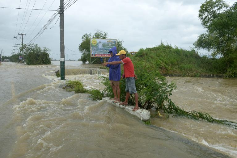Stranded commuters stand in flood waters after Typhoon Nari pummelled the northern Philippines, on October 12, 2013