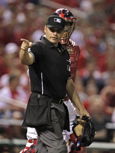 Home plate umpire Mark Wegner warns the St. Louis Cardinals bench, in front of Cardinals catcher Yadier Molina, after Houston Astros' Jason Castro was hit by a pitch in the sixth inning of a baseball game, Tuesday, July 9, 2013, in St. Louis.(AP Photo/Tom Gannam)
