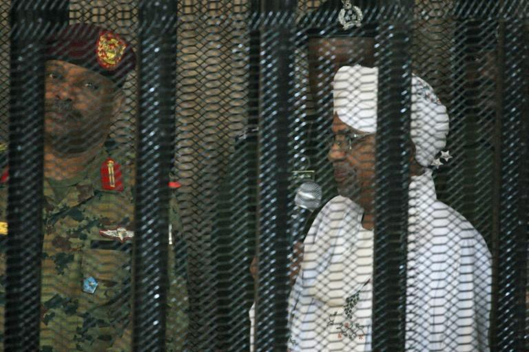 Al-Bashir stands in a defendant's cage during the opening of his corruption trial in Khartoum in August last year