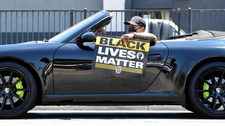 A Black Lives Matter placard is displayed by a driver from his convertible during a rally in Los Angeles in July 2020