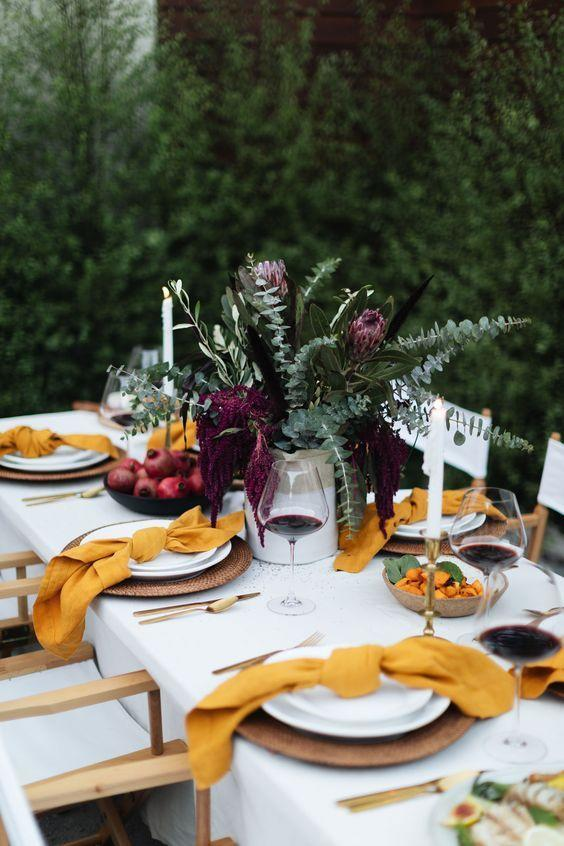 """<p>If you're feeling bold, choose a palette of jewel tones for this year's table. The bright yellowish-orange mixed with the bold plum here brings often overlooked fall colors front and center. </p><p><a class=""""link rapid-noclick-resp"""" href=""""https://withlovefromkat.com/a-fall-tablescape/"""" rel=""""nofollow noopener"""" target=""""_blank"""" data-ylk=""""slk:See more at With Love from Kat"""">See more at With Love from Kat</a></p>"""
