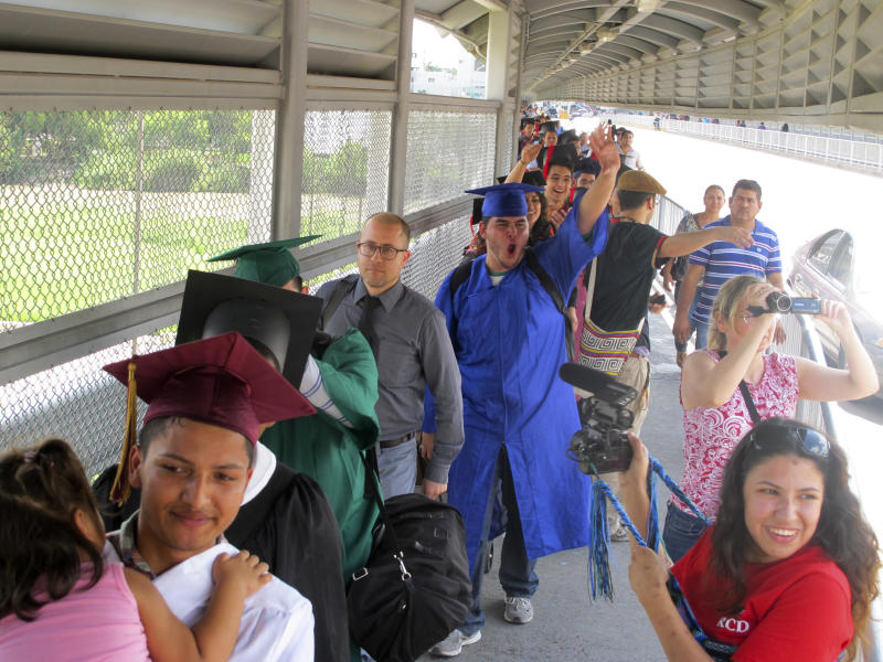 """Wearing graduation-style cap and gown, U.S.-raised immigrant Alberto Peniche, 20, born in Mexico City and raised in Boston, waves and shouts as he and nearly three dozen youth prepare to present themselves to U.S. immigration officials as they cross the international bridge in Nuevo Laredo, Mexico, Monday, Sept. 30, 2013. Peniche's sister Maria Ines was part of the original """"Dream Nine,"""" a smaller group that attempted to enter the U.S. at Nogales, Arizona, in July. (AP Photo/Christopher Sherman)"""