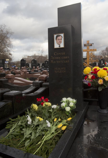 FILE - This Friday, Nov. 16, 2012 file photo shows a tombstone on the grave of lawyer Sergei Magnitsky who died in jail, at a cemetery in Moscow. Russia is preparing to put lawyer Sergei Magnitsky on trial, even though he is dead, in the latest twist in a case that has severely strained U.S.- Russian relations. Magnitsky, a lawyer for the Hermitage Capital fund, died in jail in 2009 after accusing Russian officials of colluding in stealing $230 million from the state. He was arrested on suspicion of tax evasion by the same Interior Ministry officials he accused. A Moscow court on Monday Jan. 28, 2012 set preliminary hearings in the posthumous trial for Feb. 18. (AP Photo/Misha Japaridze, file)