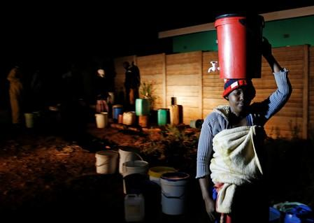 Residents collect water at night from an electric powered borehole as the country faces 18-hour daily power cuts in a suburb of Harare