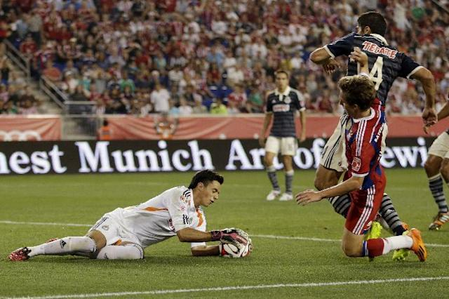 Chivas goalkeeper Antonio Rodriguez dives for the ball as Bayern Munich's Gianluca Gaudin, right, attacks during the first half of an international friendly soccer match at Red Bull Arena, Thursday, July 31, 2014, in Harrison, N.J. (AP Photo/Julio Cortez)