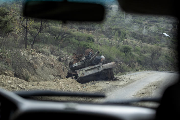 """FILE - In this Tuesday, May 11, 2021 file photo, a destroyed tank sits by the side of a road leading to Abi Adi, in the Tigray region of northern Ethiopia. Ethiopia's government said in a statement carried by state media Monday, June 28, 2021, that it has """"positively accepted"""" a call for an immediate, unilateral cease-fire in its Tigray region after nearly eight months of deadly conflict. (AP Photo/Ben Curtis, File)"""