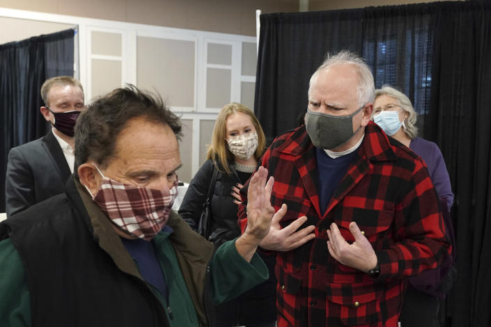 Gov. Tim Walz, right, along with Commissioner for the Minnesota Department of Health Jan Malcolm, rear right, were confronted by a man who opposed their policies as they toured a facility where COVID-19 vaccines were being administered to people with appointments at the Earle Brown Heritage Center, Thursday, Jan. 28, 2021, in Brooklyn Center, Minn. Walz toured a community vaccination clinic to highlight efforts to vaccinate Minnesotans who are 65 and over Thursday. (Anthony Souffle/Star Tribune via AP)