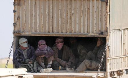 Men with covered faces sit in the back of a truck near the village of Baghouz