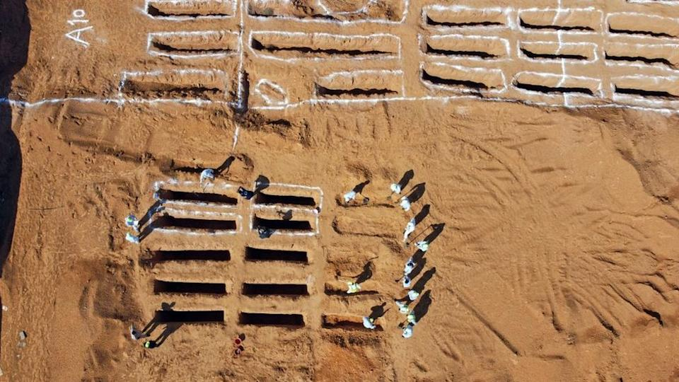 An aerial view shows Libyan experts exhuming human remains from mass graves in Tarhuna, southeast of the capital Tripoli, on October 28, 2020. - Libya's General Authority for the Search and Identification of Missing Persons reported yesterday that 12 unidentified bodies were recovered in the Rabt project area in Tarhuna.