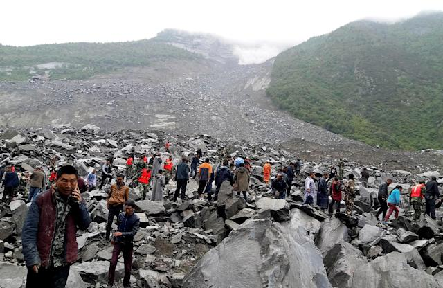 <p>People search for survivors at the site of a landslide that destroyed some 40 households, where more than 100 people are feared to be buried, local media reports, in Xinmo Village, Sichuan Province, China, June 24, 2017. (Photo: Stringer/Reuters) </p>