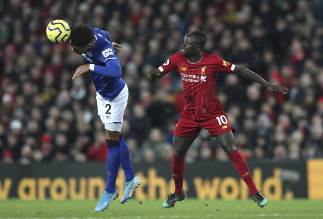Liverpool's Sadio Mane, right, challenges for the ball with Everton's Mason Holgate during the English Premier League soccer match between Liverpool and Everton at Anfield Stadium, Liverpool, England, Wednesday, Dec. 4, 2019. (AP Photo/Jon Super)